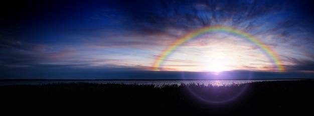 Dramatic rainbow at sunset river landscape background