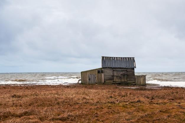 荒れ狂う白海と海岸の釣り小屋のある劇的な海の景色。カンダラクシャ湾。ウンバ。ロシア。
