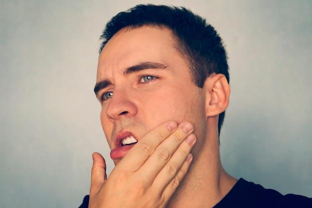 그의 턱을 잡고 고통에 남자의 극적인 샷. 치통 . 턱에 펀치. 모욕. 그 남자는 면도 후 턱을 쓰다듬었다. 구내염, 치주 질환, 발치.