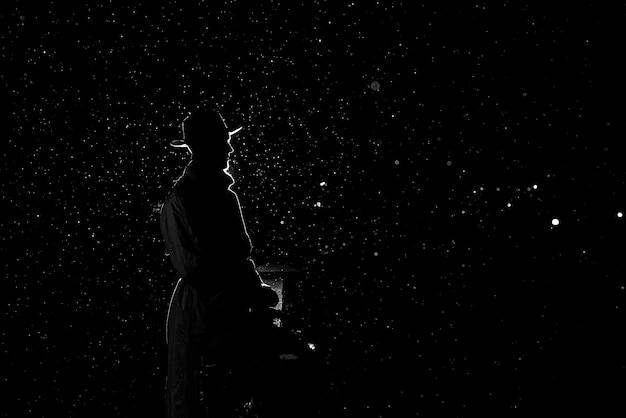 Dramatic silhouette of a dangerous man in a hat at night in the rain in the city in the old crime noir style