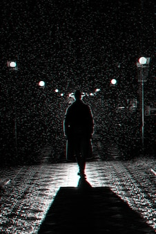 Dramatic silhouette of a man in a hat and raincoat walking through the city at night. black and white with 3d glitch virtual reality effect
