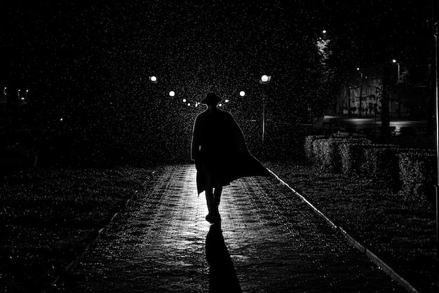 Dramatic silhouette of a man in a hat and raincoat walking through the city at night in the rain in retro noir style