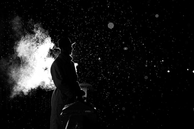 Драматический силуэт опасного человека в шляпе ночью под дождем в городе в старинном криминальном стиле нуар
