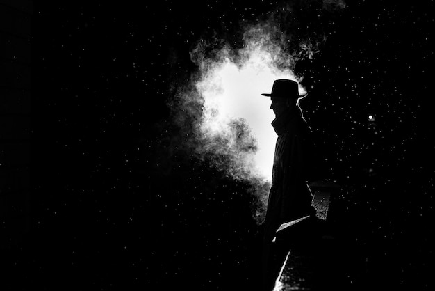 古い犯罪ノワールスタイルで街の雨の中で夜の帽子をかぶった危険な男の劇的なシルエット