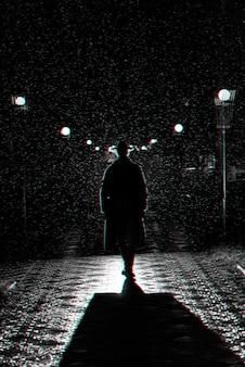 밤에 도시를 걷는 모자와 비옷을 입은 남자의 극적인 실루엣. 3d 글리치 가상 현실 효과가 있는 흑백