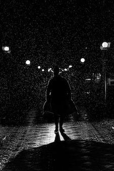 복고풍 누아 스타일의 비가 내리는 밤에 도시를 걷는 모자와 비옷에있는 남자의 극적인 실루엣
