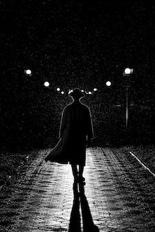 복고풍 느와르 스타일의 빗속에서 밤에 도시를 걷는 모자와 비옷을 입은 남자의 극적인 실루엣