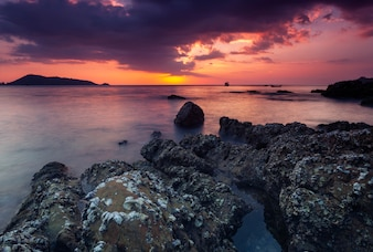 Dramatic sky and wave seascape with rock in sunset scenery background