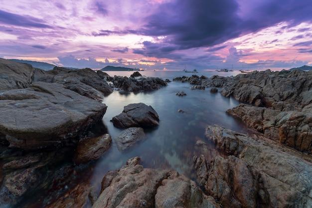 일몰 풍경 배경에서 바위와 극적인 하늘과 파도 바다