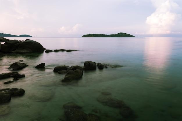 일몰 풍경에 바위와 극적인 하늘과 파도 바다