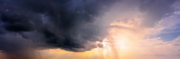 暗い雨雲から明るい太陽が差し込む劇的な空のパノラマ。