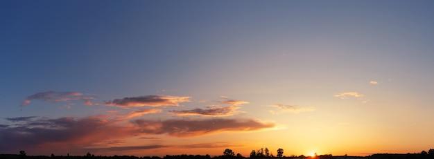 日没時の雲と劇的な空のパノラマ。太陽が地平線に沈む。