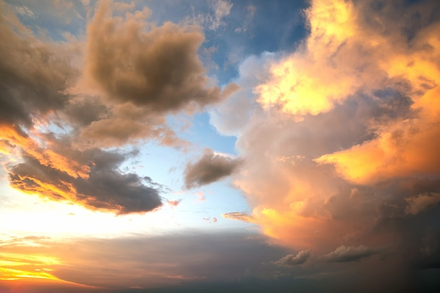 Dramatic sky at sunset with puffy clouds lit by orange setting sun.