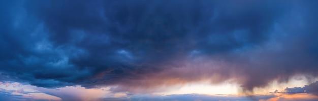 Драматическое небо с темными дождливыми облаками на закате.