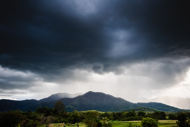 Dramatic storm clouds with rain on mountain