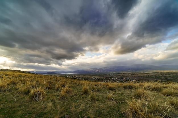 雲の間と山の向こうに太陽光線がある劇的な嵐の空の風景。暗い風景。マドリッド。