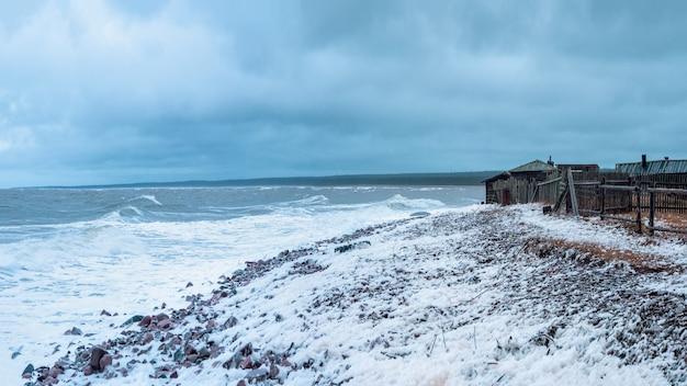 ビーチでの劇的な嵐の日。広いパノラマ。カシュカランツィ漁業集団農場。白海沿岸の小さな本物の村。コラ半島。ロシア。