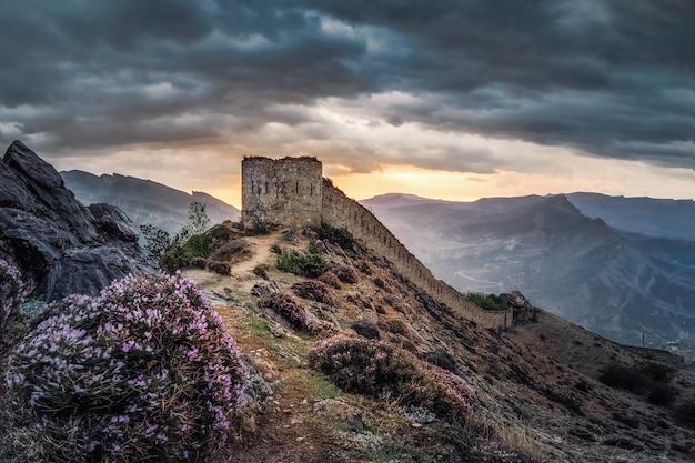 山の頂上にある古代の要塞での劇的な日の出。グニブ要塞はダゲスタンの歴史的記念碑です。ロシア。