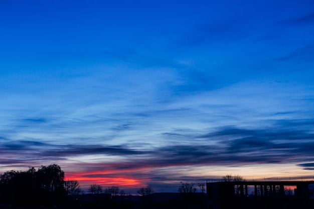 Драматическое небо заката и восхода солнца фиолетовые и синие облака
