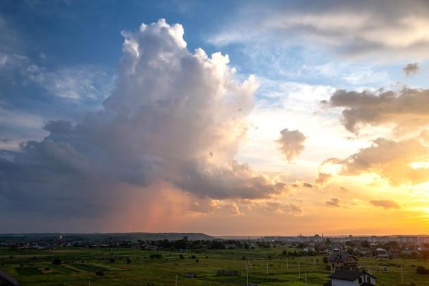 오렌지 석양과 푸른 하늘에 의해 조명 폭풍우 푹신한 구름과 농촌 지역의 극적인 일몰 풍경.