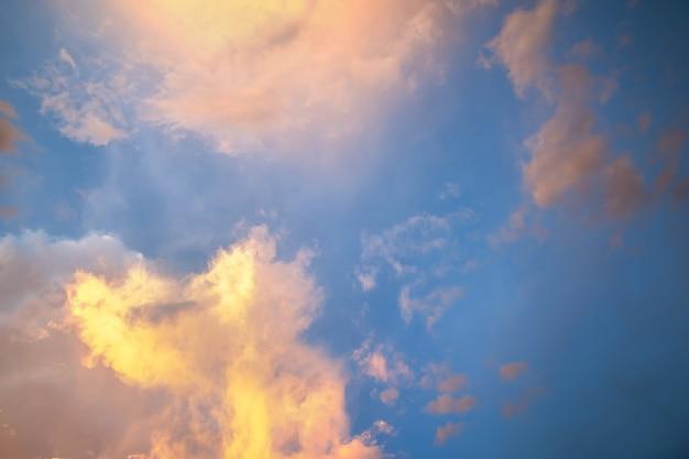 푹신한 구름이 있는 극적인 일몰 풍경 사진은 오렌지색 석양과 푸른 하늘을 비추고 있습니다.