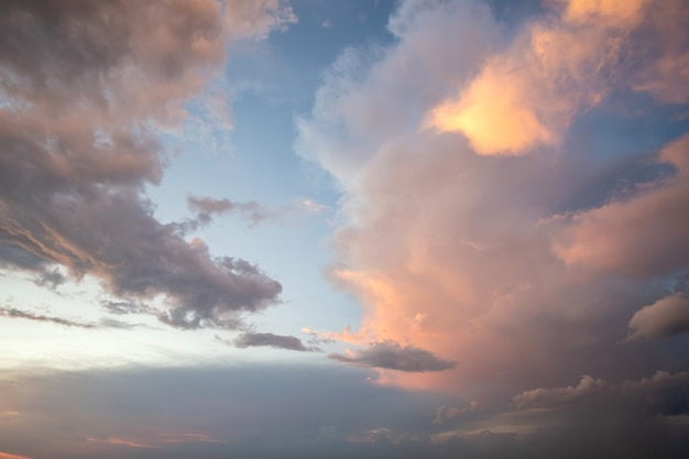 Драматический пейзаж заката с пухлыми облаками, освещенными оранжевым заходящим солнцем и голубым небом.