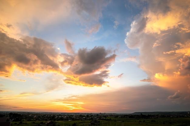 푹신한 구름이 있는 극적인 일몰 풍경은 오렌지색 석양과 푸른 하늘을 비추고 있습니다.