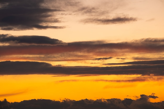 Dramatic sunset landscape with puffy clouds lit by orange setting sun and blue sky.
