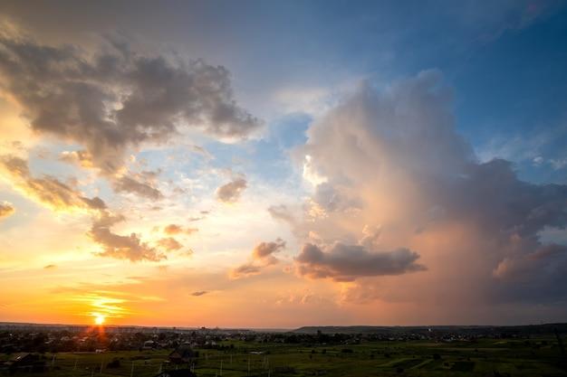 Драматический закат над сельской местностью с грозовыми облаками, освещенными оранжевым заходящим солнцем и голубым небом.