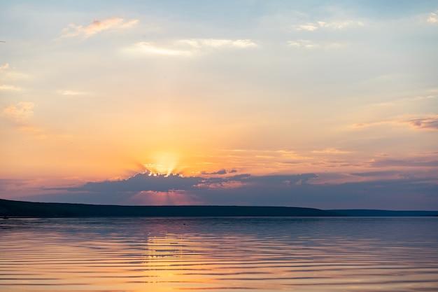 Драматический закат над морской водой с пасмурным небом золотой цвет фона природы со спокойной водой