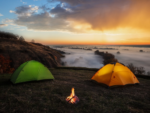 Драматический закат над рекой и палатками с костром