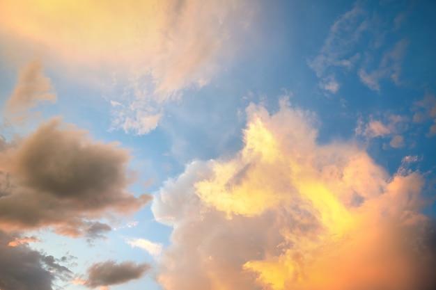 Драматический пейзаж закатного неба с пухлыми облаками, освещенными оранжевым заходящим солнцем и голубыми небесами