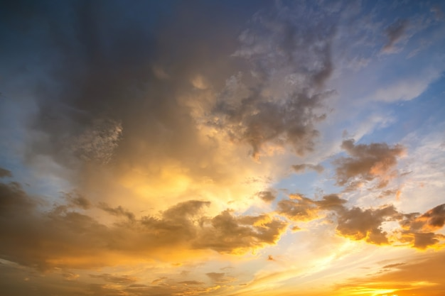 Драматический пейзаж закатного неба с пухлыми облаками, освещенными оранжевым заходящим солнцем и голубыми небесами.