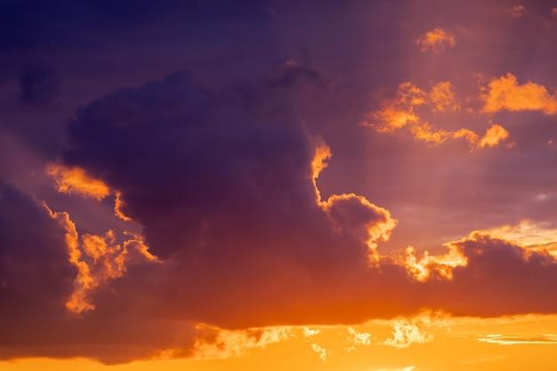 Драматическая панорама неба заката с горящей красочной поверхностью облаков.