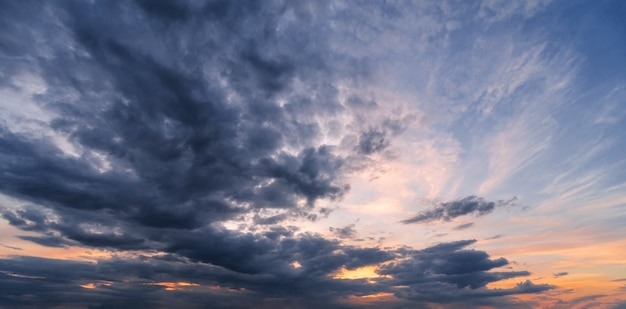 暗い雲と劇的な夕焼け空。夕暮れ時の美しい雲景。