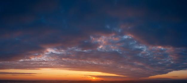 극적인 일몰, 태양 광선이 구름을 통해 빛납니다.