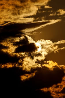 구름과 극적인 일몰입니다. 둥근 태양이 앉는다.