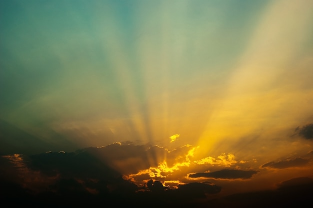 Dramatic twilight sky blurred background with sun beams and golden lining.