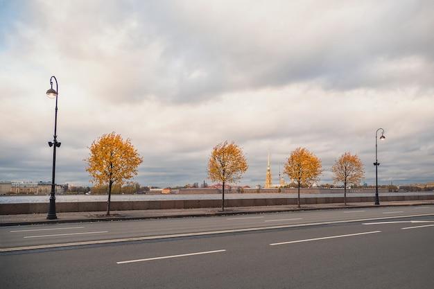 秋の街の劇的な眺め。サンクトペテルブルクの花崗岩の堤防にある黄色い秋の木々。ロシア。