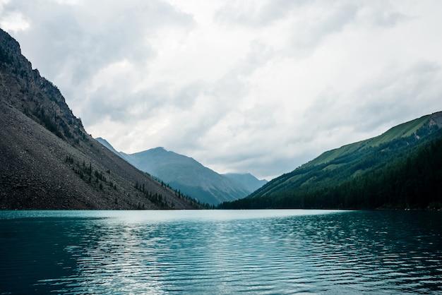 雨天時の巨大な山々に囲まれた広大な山岳湖を一望。紺碧の水の近くの丘の中腹に松とカラマツ。ターコイズブルーの高山湖のある曇った風景。大気の高原の風景。