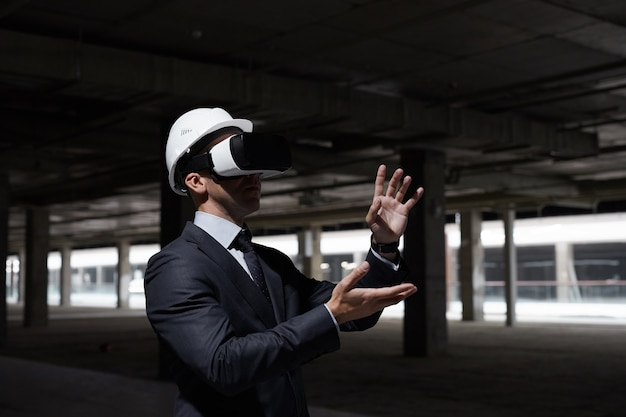 미래의 프로젝트를 3d로 시각화하면서 건설 현장에서 vr 장비를 착용 한 사업가의 극적인 허리 초상화,