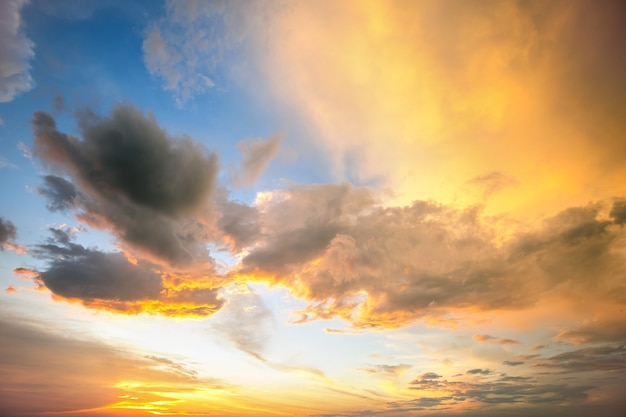 Dramatic yellow sunset landscape with puffy clouds lit by orange setting sun and blue sky.
