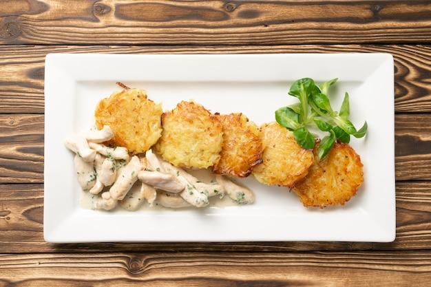 Драники с куриным филе и сливочным соусом в белой керамической тарелке