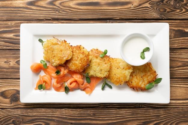 Драники с маринованным лососем и сметаной в белой керамической тарелке