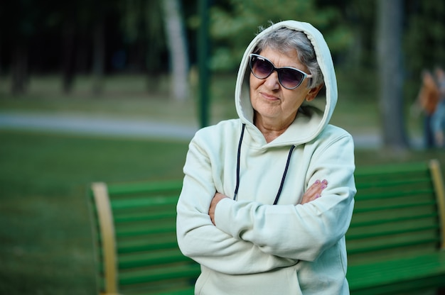 夏の公園でパーカーとサングラスのレジャーでドラニー。高齢者のライフスタイル。屋外で楽しんでいるかなりファッショナブルな祖母、自然の中で年配の女性