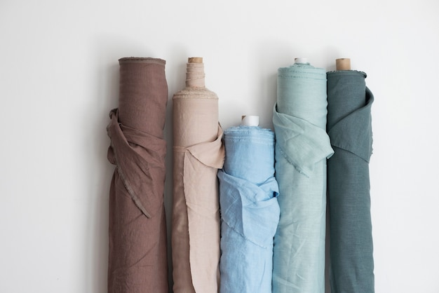 Drapery shop concept. rolls of different colors linen on the light wall, selecrive focus image