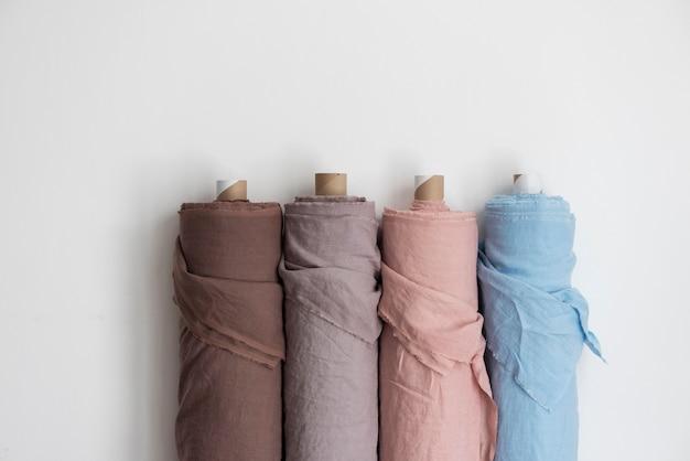 Концепция магазина драпировки. рулоны разноцветного белья на светлой стене, селективный фокус изображения