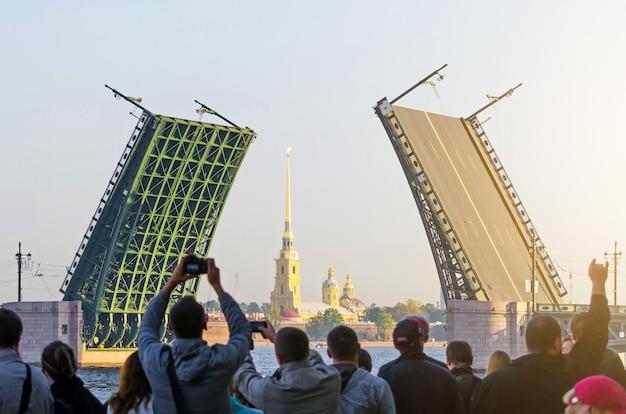 Дворец подъемного моста днем и петропавловская крепость с толпой людей, наблюдающих за зрелищем.