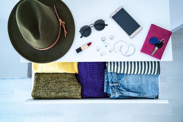 Комод с стильной повседневной модной одеждой, домашними вещами и женскими аксессуарами. вид сверху. выбор, что надеть