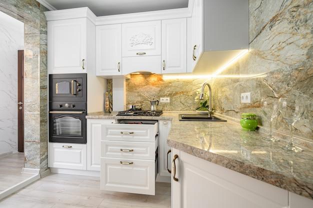 Выдвинутые ящики на современной классической белой кухонной мебели